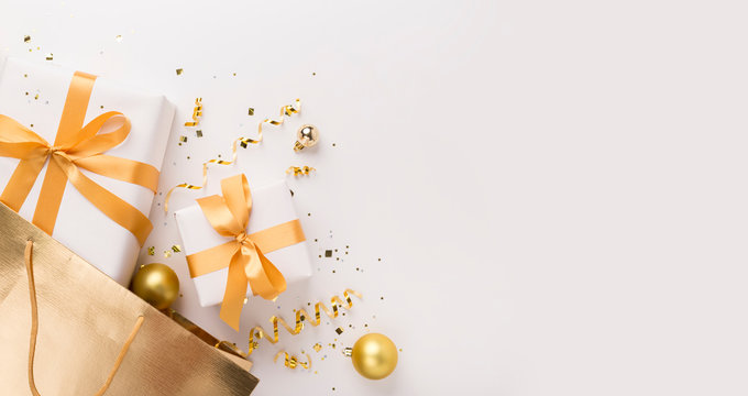 Present boxes with gold ribbon inside shopping bag on white
