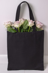 Black cotton tote bag with light violet roses inside. Styled photography