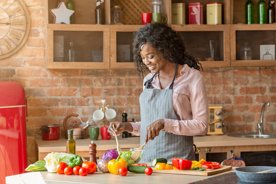 Attractive woman cooking healthy salad at kitchen