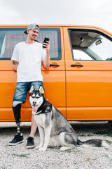 Young man with dog wearing leg prosthesis and using cell phone at camper van