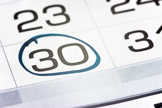 the thirtieth day of the month highlighted on the calendar close-up macro, the mark on the calendar, the thirtieth date