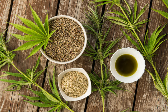 Hemp leaves, seeds and oil from above on wooden background