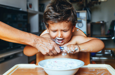 Little boy eating yogurt at home, hand of woman on the spoon