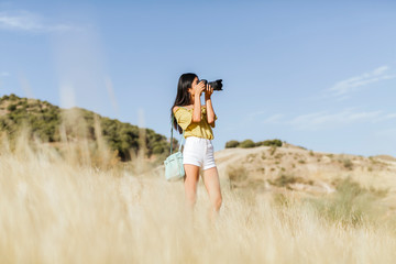 Young woman taking pictures in remote landscape, Granada, Spain