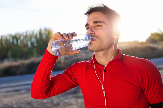 Young jogger drinking from a water bottle