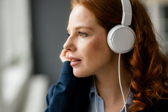 Portrait of redheaded businesswoman listening music with white headphones