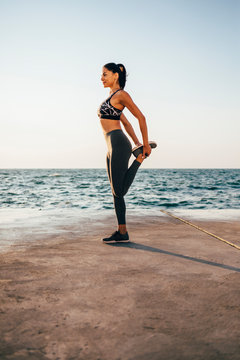 Young sports woman stretching her leg on a pier