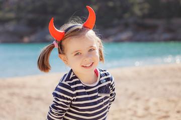 Portrait of girl on the beach wearing devil's horns
