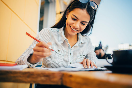 Smiling young woman taking notes in a cafe