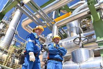 Industriearbeiter in Erdölraffinerie // chemical industry plant - workers in work clothes in a refinery with pipes and machinery