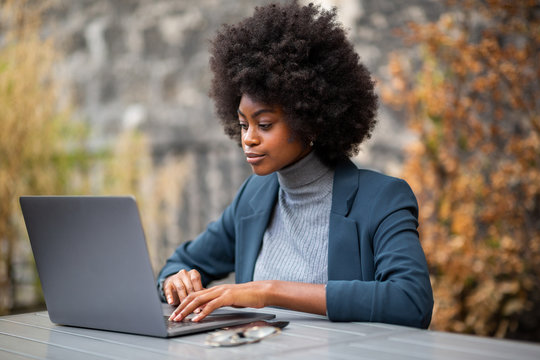 serious young black business woman sitting with laptop
