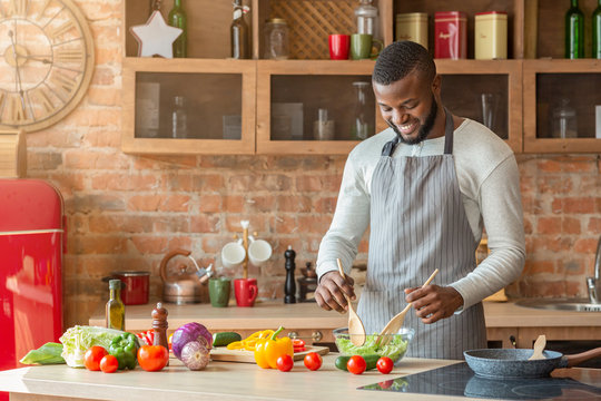 Handsome man preparing fresh healthy salad at kitchen