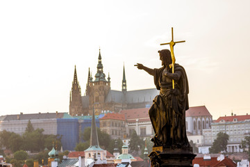 Sculpture of John the Baptist on Charles bridge against the Prague castle.