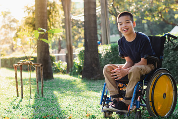 Disabled child on wheelchair is playing, learning and exercise in the outdoor city park like other...