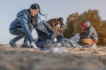 Group of young people cleaning beach area