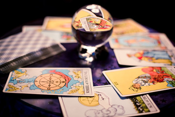 Tarot cards spread on a table surrounding crystal ball