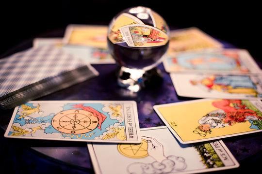Tarot cards spread on a table surrounding crystal ball