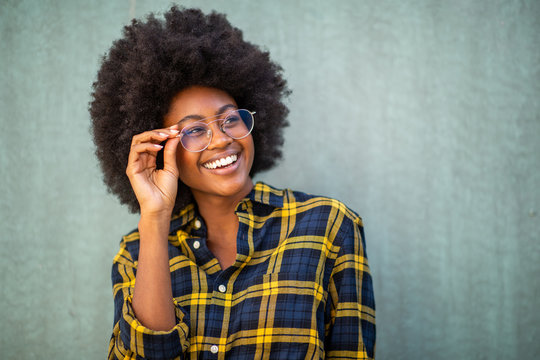 Close up young afro woman holding glasses and smiling against green background