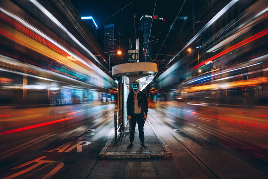 Time lapse photography of man standing in the middle of the street