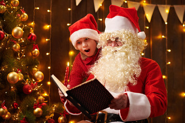 Santa Claus and santa helper boy reading book, sitting indoor near decorated xmas tree with lights - Merry Christmas and Happy Holidays!