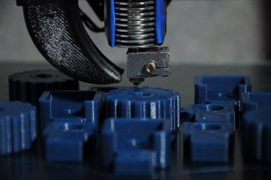 Close-up of 3D printed parts made of blue plastic and the print head of the printer