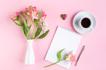Greeting card concept. Bouquet of Alstroemeria in a white vase, a cup of black coffee, pen and notebook on a pink paper background. Top view