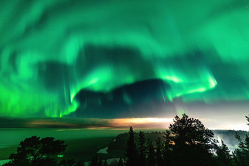 Papiers peints Aurore polaire View of brilliant green Aurora shining over Swedish foggy forest landscape in mountains, light rays from a village and Northern Lights color sky in different soft colors, Northern Sweden, Scandinavia