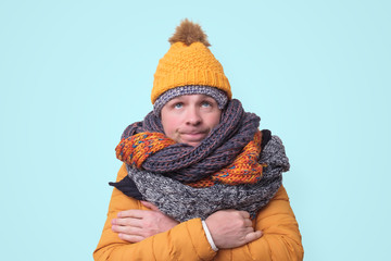 Obraz Handsome caucasian funny man in several hats and scarfs. - fototapety do salonu