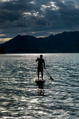Silhouette man paddleboarding on sunny, idyllic lake, Walchensee, Bavaria, Germany
