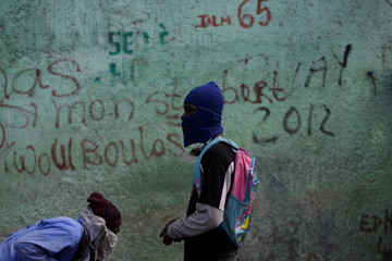 A protester runs away as another one looks on during clashes with residents at Delmas 65, during a protest to demand the resignation of Haitian president Jovenel Moise, in the streets of Port-au-Prince