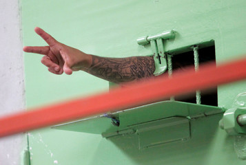 A gang member makes signs from inside his cell during a media tour to the newly open high security area of the Tamara prison, on the outskirts of Tegucigalpa
