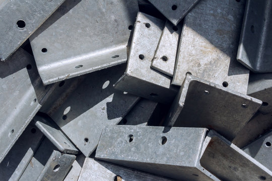 Industrial background. Sheet metal parts for attaching metal beams to each other.