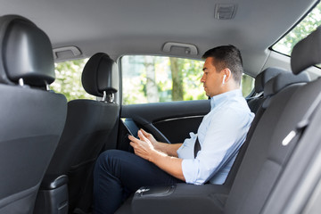 transport, business and technology concept - male passenger or businessman with wireless earphones using tablet pc computer on back seat of taxi car