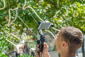Male blogger shoots on phone with Steadicam video on a Sunny summer day close-up