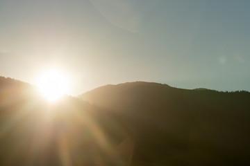 Sunny autumn mountain scene with sun ray