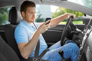 transport, vehicle and technology concept - smiling man or driver driving car and using smartphone