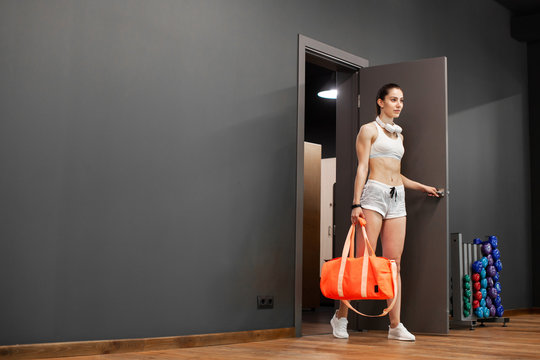 Sexy athletic girl enters the gym. Sportswoman opens the door to the locker room. Stylish black interior of modern fitness gym. Concept of health. European brunette girl holding a sports bag..