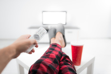 Man drinking soda juice and looking at TV with legs on the table in living room.