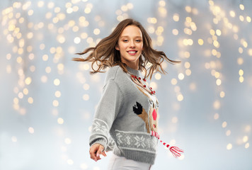 christmas, people and holidays concept - happy young woman in jumper with reindeer pattern dancing...