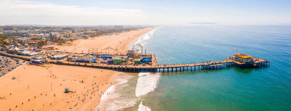 Aerial view of Santa Monica Pier, California - USA. Beautiful amusement park with ferris wheel and roller coaster.
