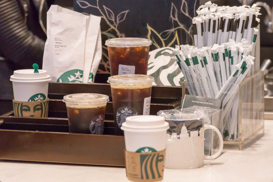NEW YORK, USA - MAY 15, 2019: Counter in Starbucks cafe with Straws and beverages to pick up to go