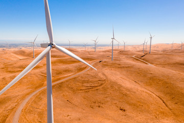 Aerial view of the wind turbines on beautiful golden mountain landscape in California. Curvy road through the mountains. Green ecological power energy generation. Wind farm clean eco energy