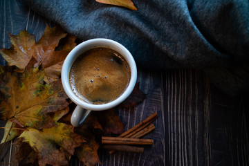 Cup of coffee with fig's leaves, cinammon sticks and a grey blanket on a wooden table.