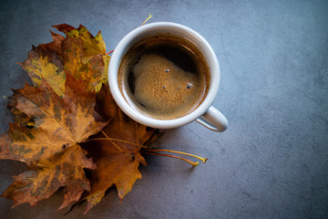 Cup of cafe latte on concrete background with orange autumn leaves. Copy space.