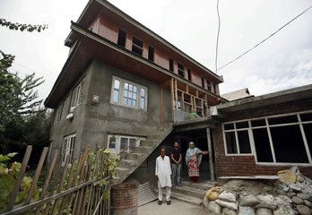 Mohammad Maqbool Malik, Haseena and Danish, parents and brother of Uzair Maqbool Malik pose for a picture outside their house in south Kashmir's Shopian