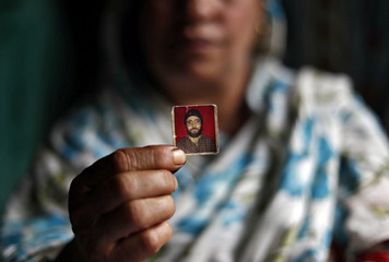 Haseena Malik shows a photograph of her son Uzair Maqbool Malik at her house in south Kashmir's Shopian