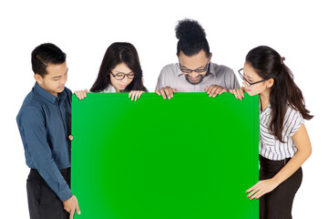 Business team looking at an empty green board