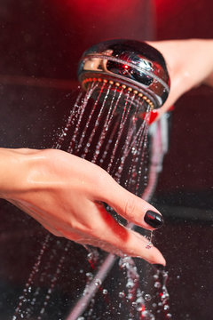 Two lesbian girls in the shower. Shower head with pouring water and a female hand