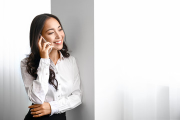 Beautiful Asian woman talking by phone in office