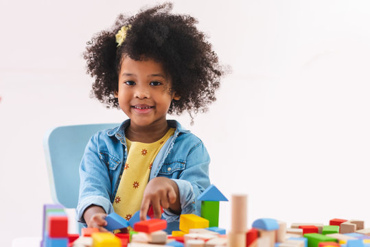 Little afro girl smiling and playing colorful wooden toys.